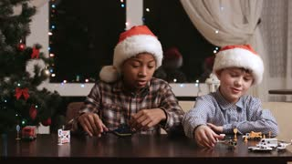 Christmas kids playing with toys. Boys play with toy vehicles. Careless friends spend time together. Playful boys in Santa hats.