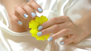Chysanthemum in manicured hands, slow motion. Well-groomed hands with stylish manicure holding yellow flower on white silk background close up. Softness and purity concept.
