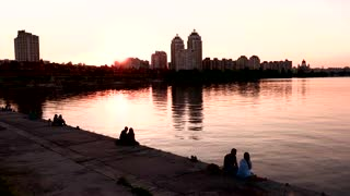 City buildings near water. Couples sitting on embankment. Romantic and quiet place. Clear evening sky.
