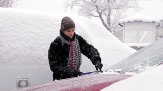 cleaning car brush off the snow