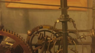 Clock mechanism in motion. Pendulum and cogwheels.