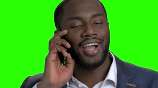 Close up african american guy talking on phone. Cheerful afro american man in formal wear talking on cell phone on Alpha Channel background.