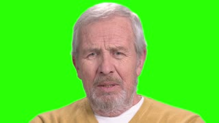 Close up elderly man is talking, green screen. Senior man speaking and gesturing with hands, alpha channel background. Tells of an interesting information.
