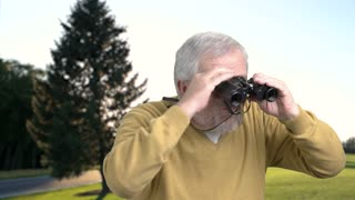 Close up elderly man looking through binoculars. Senior caucasian explorer using binoculars on nature background. Aged man looking for something with binoculars.
