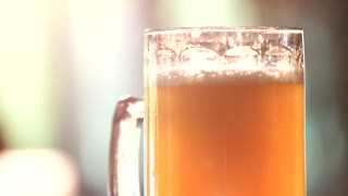 Close up glass of light ale rotating. Glass of fresh brewed craft lager beer.
