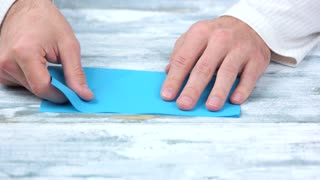 Close up hands folding blue paper sheet. Japanese paper folding workshop. Modern paper craft.