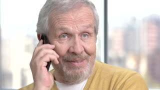 Close up male senior talking on phone. Handsome senior man with mobile phone close up. People, technology, lifestyle.