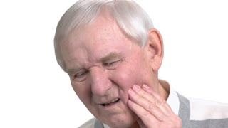 Close up man suffering from toothache. Old man with toothache, white background. How to stop toothache. Remedy for tooth ache.