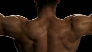 Close up mans lifting dumbbels, back view. Sportsman having workout at gym. Close up on bicep muscles of a professional bodybuilder.