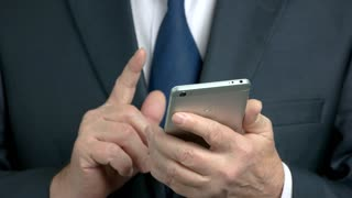 Close up mature businessman using smartphone. Elderly man in business suit typing a message on his smartphone close up.