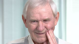 Close up mature man having toothache. Unhappy senior man touching his cheek outside and suffering from teeth pain, blurred background.