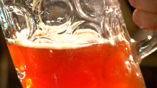 Close up mug filling with red ale, slow-motion. Middle of mug with filling beer.