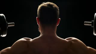 Close up muscular man lifting dumbbells. Powerful mans body, back view. Beautiful lines of silhouette over black background.