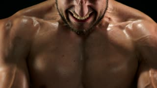 Close up muscular sweaty chest of sportsman. Toned male body doing exercises with rubber band close up. Hard efforts in muscles building.