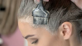 Close up of hair dying. Brush is applying hair color. Shocking facts about hair dye.