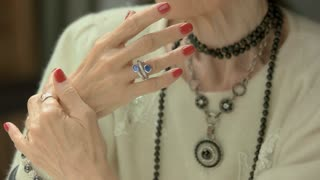 Close up of well-groomed female hands. Old woman hands with beautiful red manicure and luxury jewelry on fingers. Beauty and aristocratism concept.
