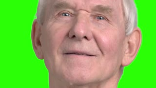 Close up old man face motion. Facial expressions of senior man looking forward, green background for keying.