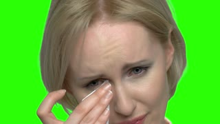 Close up portrait beautiful sad crying woman. Green hromakey background for keying.