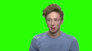Close up portrait of angry boy shouting. Upset and angry boy concept for anger. Green screen hromakey background for keying.