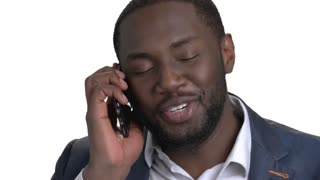 Close up portrait of black businessman talking on phone. African american man in suit talking emotionally on phone. White isolated background.