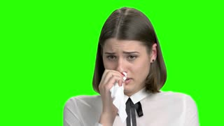 Close up portrait of crying teen student girl. Green screen hromakey background for keying.
