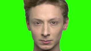 Close up portrait of tired teenage boy rubbing eyes. Green screen hromakey background for keying.