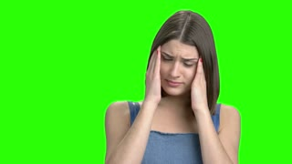 Close up portrait of woman having head pain. Green screen hromakey background for keying.