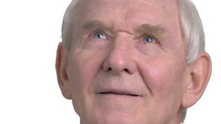 Close up senior man looking upwards. Elderly man dreaming isolated on white background close up.