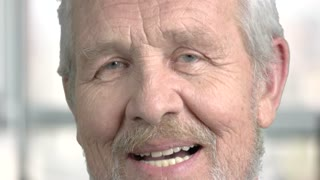 Close up senior man nodding with head. Face of grey haired pensioner close up. Human suspicious expression.