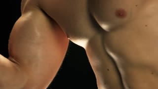 Close up shirtless man doing arm exercise. Young man building muscles with dumbbell close up. Strength training for better health.