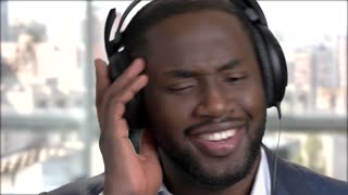 Close up smiling face of businessman in headphones. Cheerful african-american man listening to music in headphones close up.