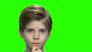 Close up thinking boy touching chin. Green hromakey background for keying.