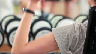 Close up woman lifting dumbbell. Woman flexing hand with dumbbell, back view. Biceps building for women.
