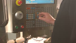 Cnc lathe control panel. Hand of man pushing buttons. Enter the right data.
