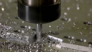 Cnc milling machine working. Drill and metal shavings.