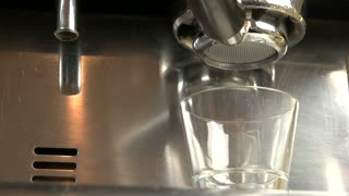 Coffee machine with bottomless portafilter. Espresso dripping into a glass.