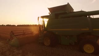 Combine and field at sunrise. Agriculture and technology.