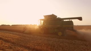 Combine harvester and sunrise. New farm equipment.
