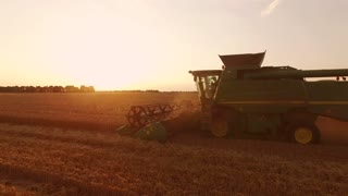 Combine harvester at sunrise. Modern farming methods.