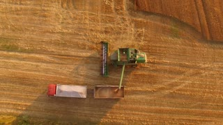 Combine unloads grain. Agricultural machines aerial view.