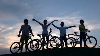 Company of young cyclists at sunset sky. Group of young people with bicycles waving with hands on sky background. Best rest outdoors.