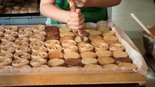 Confectioner decorating biscuits with yummy cream. Baker covers cakes with cream in kitchen in pastry shop. Manufacturing of pastry at food factory.