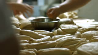 Confectioners knead the dough. Hand kneading. Women make cakes. Manufacture of bakery products. Organic bakery.