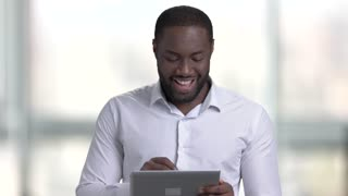 Confident afro american with tablet. Happy black man in white shirt against windows background.