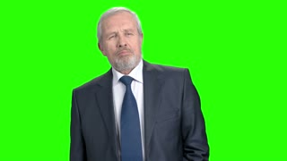 Confident elderly businessman, green screen. Senior caucasian business man looking displeased and nodding with head on chroma key background.