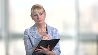 Confident female supervisor with black clipboard. Elegant mature woman making note on clipboard on blurred background. Inspection and documentation.