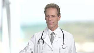 Confident male doctor with syringe. Mature professional doctor holding syringe on blurred background. People, profession and healthcare.