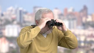 Confident mature man with binoculars. Senior man with binoculars on city background.