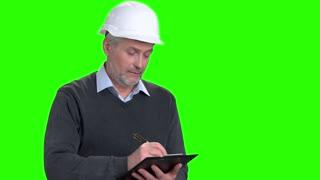 Confident mature supervisor writing on clipboard. Senior man in white helmet writing on black clipboard on chroma key background.