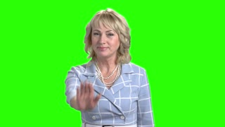 Confident mature woman making gesture stop. Elegant middle-aged business woman gesturing stop sign on chroma key background. Human body language.